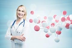 Doutor louro da mulher perto de uma molécula fotos de stock