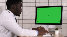 Doutor maduro que trabalha no computador Indicador branco filme