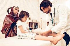 Doutor masculino árabe Bandaging Limb do paciente da criança fotos de stock royalty free