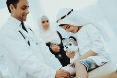 Doutor masculino árabe Bandaging Limb do paciente da criança foto de stock
