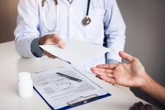 Doutor masculino asiático que fala na sala da clínica e que entrega uma prescrição fotografia de stock