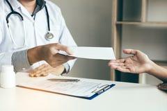 Doutor masculino asiático que fala na sala da clínica e que entrega uma prescrição fotografia de stock royalty free