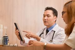 Doutor masculino asiático que usa o tablet pc digital fotografia de stock