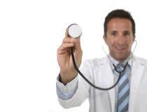 doutor masculino atrativo da medicina 40s no vestido médico com fim acima da mão que mantém o sorriso do estetoscópio feliz Imagens de Stock