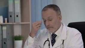 Doutor masculino cansado que pensa sobre os casos médicos que ocorreram em sua prática vídeos de arquivo