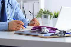 Doutor masculino com estetoscópio médico usando um portátil, sentando-se em sua mesa fotografia de stock royalty free