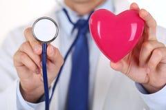 Doutor masculino da medicina que guarda o coração e o estetoscópio vermelhos Fotografia de Stock