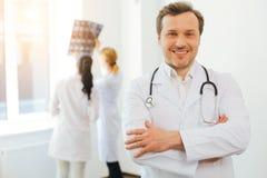 Doutor masculino de irradiação que levanta com os braços cruzados Imagem de Stock
