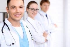 Doutor masculino de sorriso alegre com o pessoal médico no hospital Fotos de Stock