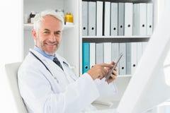 Doutor masculino de sorriso que usa a tabuleta digital no escritório médico imagens de stock