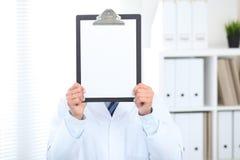 Doutor masculino desconhecido que está reto ao guardar a prancheta médica com Livro Branco vazio em vez de sua cara Foto de Stock