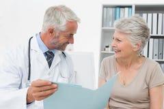 Doutor masculino e paciente superior com relatórios fotos de stock
