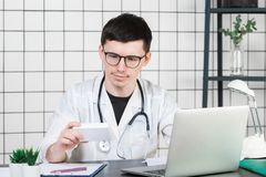 Doutor masculino no revestimento branco com o estetoscópio sobre seu pescoço que senta-se na tabela que pensa na prescrição, escr foto de stock royalty free