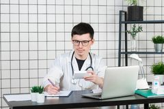 Doutor masculino no revestimento branco com o estetoscópio sobre seu pescoço que senta-se na tabela que pensa na prescrição, escr fotos de stock