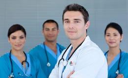 Doutor masculino novo com sua equipe no fundo Fotografia de Stock Royalty Free