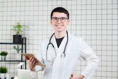 Doutor masculino novo considerável de sorriso que usa o tablet pc Tecnologias no conceito da medicina fotos de stock