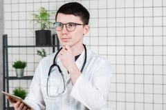 Doutor masculino novo considerável pensativo que usa o tablet pc Tecnologias no conceito da medicina imagem de stock