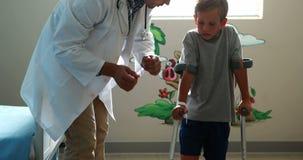 Doutor masculino que ajuda ao menino ferido a andar com muletas video estoque