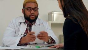 Doutor masculino que assina o papel médico em troca do dinheiro paciente fêmea vídeos de arquivo