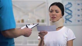 Doutor masculino que dá a conta ao paciente chocado no colar da espuma, medicina cara filme