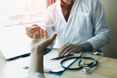 Doutor masculino que entrega uma prescrição ao paciente fotografia de stock royalty free