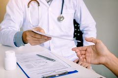 Doutor masculino que entrega uma prescrição ao paciente foto de stock royalty free