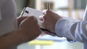 Doutor masculino que escreve para baixo queixas pacientes, dor de estômago, maré baixa ácida, úlcera filme