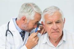Doutor masculino que examina a orelha do paciente superior Foto de Stock Royalty Free