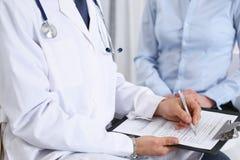 Doutor masculino que guarda o formul?rio de candidatura ao consultar o paciente f?mea no hospital Conceito da medicina e dos cuid imagens de stock