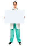Doutor masculino que indica a placa de anúncio branca Fotografia de Stock Royalty Free