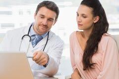 Doutor masculino que mostra algo no portátil ao paciente Imagens de Stock