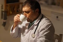 Doutor masculino que relaxa em casa imagens de stock royalty free