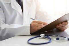 Doutor masculino que senta-se na mesa e que escreve notas na prancheta foto de stock