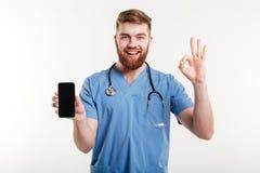 Doutor masculino que sorri com telefone e que mostra o gesto Imagem de Stock Royalty Free