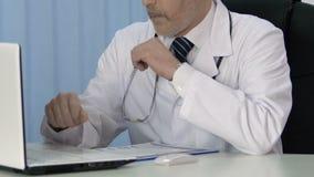 Doutor masculino que trabalha no portátil, introduzindo dados no informe médico para o seguro vídeos de arquivo