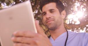 Doutor masculino que usa a tabuleta digital no quintal video estoque