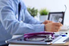 Doutor masculino que usa um portátil com o estetoscópio médico, sentando-se em sua mesa fotos de stock