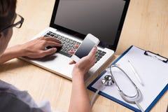 Doutor masculino que usa um portátil e um smartphone, sentando-se em sua mesa foto de stock royalty free