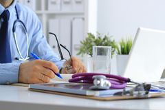 Doutor masculino que usa um portátil, sentando-se com o estetoscópio médico em sua mesa imagem de stock royalty free