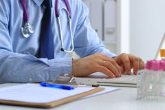 Doutor masculino que usa um portátil, sentando-se em sua mesa imagem de stock