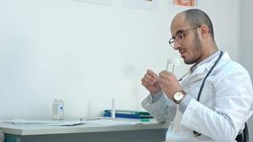 Doutor masculino que verifica a temperatura no termômetro e que enche-se no formulário médico foto de stock royalty free