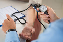 Doutor Measures Pressure In o paciente Imagens de Stock Royalty Free