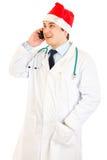 Doutor no chapéu de Papai Noel que fala no móbil Fotografia de Stock Royalty Free