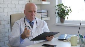 Doutor no começo do escritório do hospital que escreve uma receita médica fotos de stock