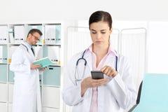 Doutor no telefone, com o colega no escritório médico fotografia de stock