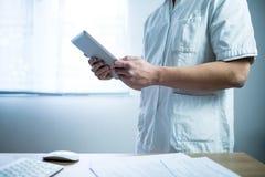 Doutor no uniforme usando a tabuleta do computador ao lado de sua mesa de escritório no hospital imagem de stock royalty free