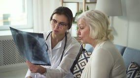 Doutor novo e mulher adulta madura que furam o raio X nas mãos video estoque