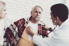 Doutor novo no revestimento que visita pares velhos em casa imagens de stock