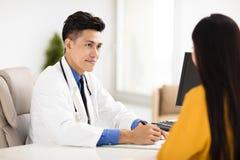 Doutor novo que fala com seu paciente no escritório imagens de stock