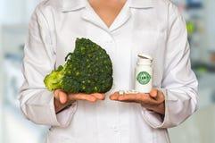 Doutor novo que guarda brócolis e a garrafa frescos dos comprimidos com vit imagens de stock